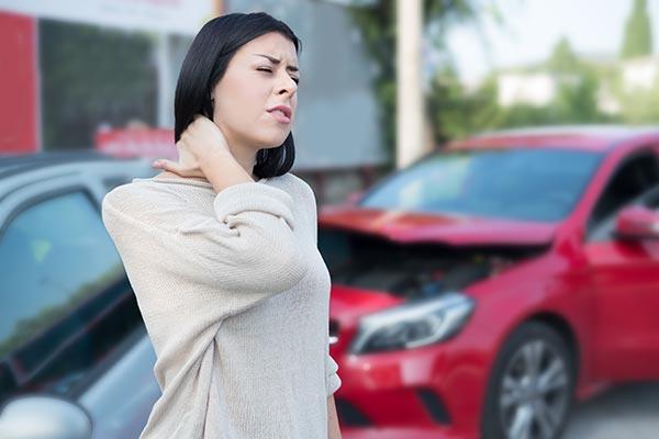Mujer con dolor de cuello después de un accidente de carro