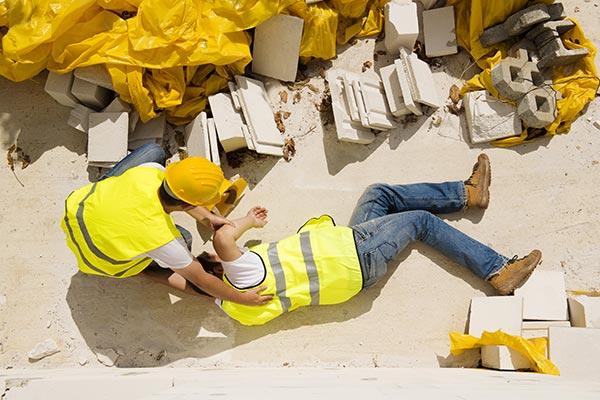 Trabajador lastimado en el suelo siendo ayudado por un amigo