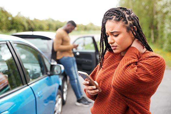 Mujer en su teléfono buscando asistencia después de un accidente de auto